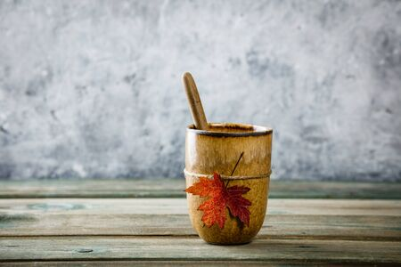 Cup of tea or coffee with autumn leaf on wooden tabel against old rust condition vintage wall, space for text