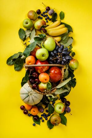 Flat-lay of fresh fruits and berries on yellow background