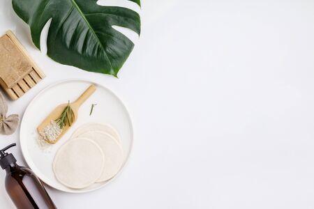 Cuscinetti riutilizzabili per la rimozione del trucco in cotone, struccante in un contenitore di vetro, spazzolino da denti in bambù ecologico naturale, sapone naturale fatto a mano, bastoncini per le orecchie di bambù, sale da bagno alle erbe. Concetto di stile di vita sostenibile. Prodotti cosmetici a scarto zero, flat lay Archivio Fotografico