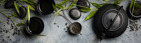 Bamboo branches and green tea on concrete background