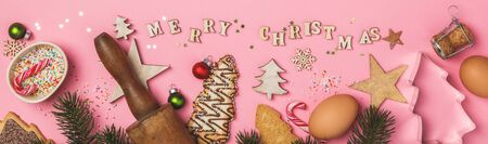 Christmas gingerbread cookies in the shape of a Christmas tree and Merry Christmas written with wooden letters