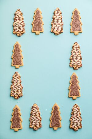 Christmas gingerbread cookies in the shape of a Christmas tree on blue background