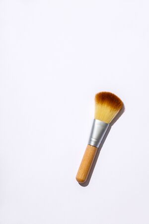 Wooden makeup brush on a white background