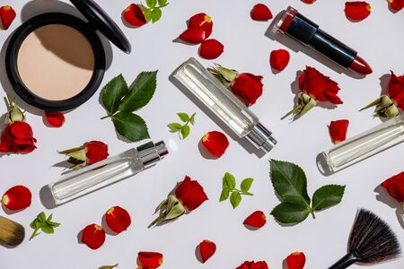 Bottles of woman perfume with cosmetic products and red roses on white background
