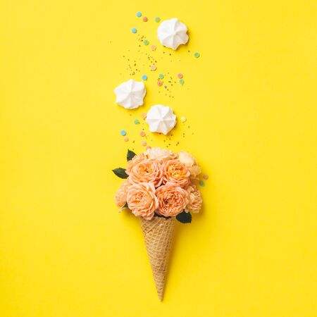 Ice cream cone with pink roses and merengues on yellow background