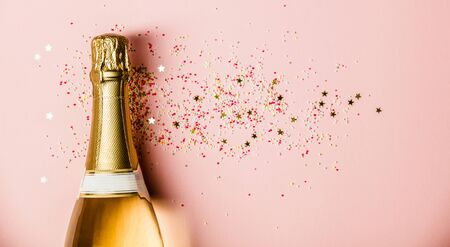 Flat lay of Celebration. Champagne bottle with sprinkles on pink background. Stok Fotoğraf