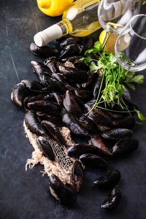 Bowl with fresh raw mussels with white wine, lemon and parsley on dark background, ready to cook