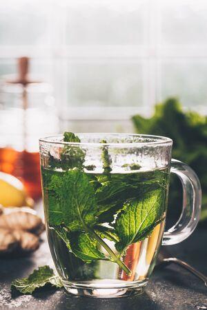 Fresh mint tea near the window. Cozy home or health concept