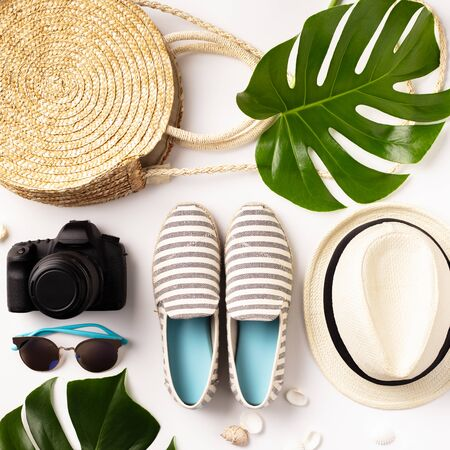 Colorful summer female fashion outfit flat-lay. Straw hat, camera, bag, summer shoes, sunglasses, shells and tropical leaves over white background, top view. Summer fashion, holiday concept, space for text