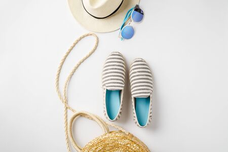 Flat lay traveler accessories on white background with straw hat, summer shoes, bag and sunglasses. Top view travel or vacation concept. Summer background. Space for text