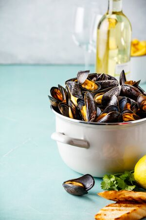 Belgian mussels in white wine with lemon, herbs, croutons and french fries on blue background Banque d'images