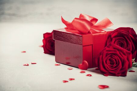Valentines Day concept. Valentines gift boxes tied with a red satin ribbon bow and beautiful roses on rustic background.