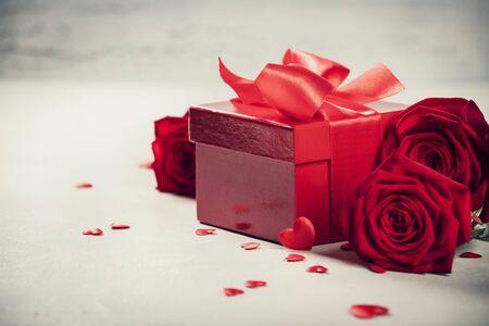 Valentinstag-Konzept. Valentinsgruß-Geschenkboxen, die mit einem roten Satinbandbogen und schönen Rosen auf rustikalem Hintergrund gebunden sind.