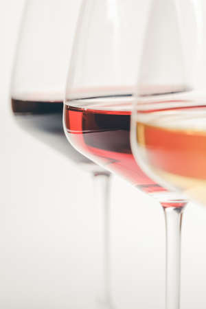 Glasses of white, red and rose wine over white background, close up