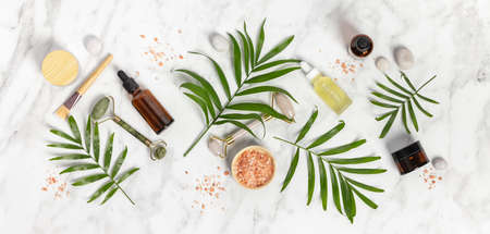 Natural SPA cosmetic products background, Composition with bottles of essential oils, sea salt and massage rollers on white marble background