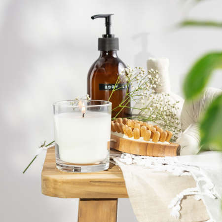 White scented candle, body lotion, anti-cellulite dry massage brush, herbal balls and delicate flowers on wooden bench