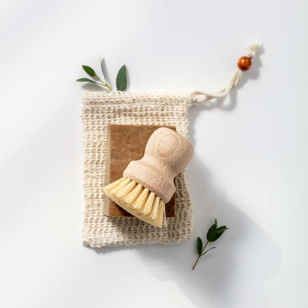 Eco friendly natural cleaning tools and products, Solid soap and natural dish brush on white background.
