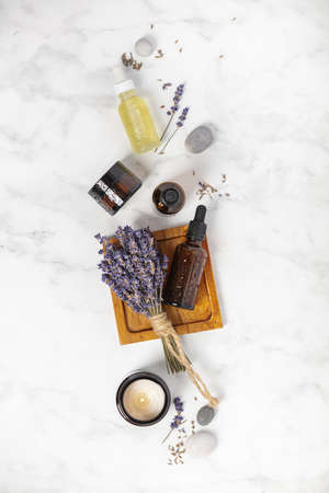 Flat lay composition with lavender flowers and natural cosmetic on white marble background