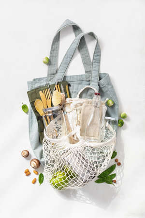 Plastic free set with cotton bags, glass jars and bamboo cutlery top view. Zero waste, eco friendly shopping concept. Flat lay. Reklamní fotografie