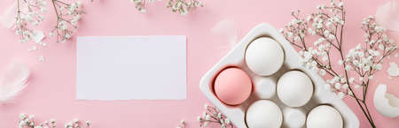 Easter eggs in white ceramic holder and flowers on pink background