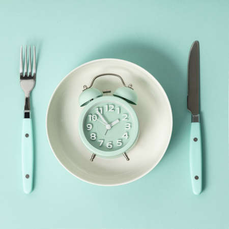 Composition with cutlery, plate and alarm clock on color background. Diet concept