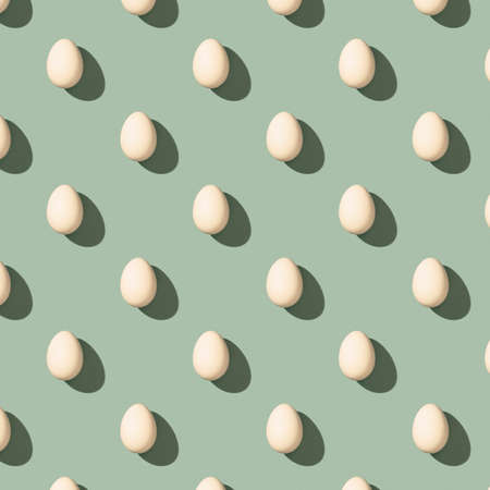 Pattern made of white eggs on pastel green background. Minimal food concept. Flat lay