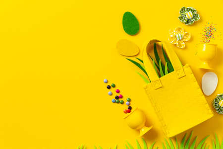 Felt Easter decorations and sweets on yellow background Reklamní fotografie
