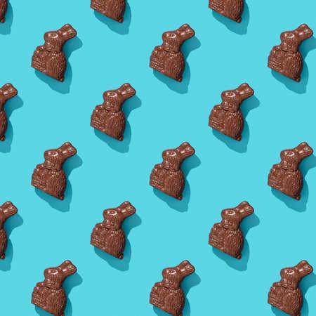 Chocolate Easter Bunny on blue background pattern, flat lay Reklamní fotografie - 165311900