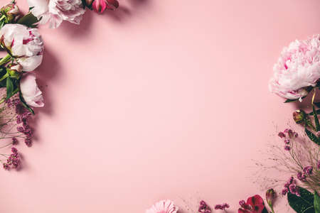 Assorted pink flower border on pink background, flat lay