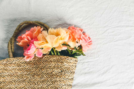 Flat-lay of Beautiful peony flowers in straw bag over grey linen table cloth background