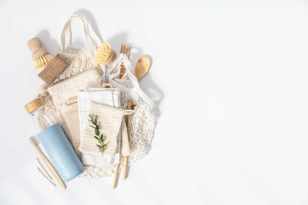 Plastic free set with cotton bags, cleaning tools, Reusable bottle, bamboo cutlery and toothbrushes top view on white background