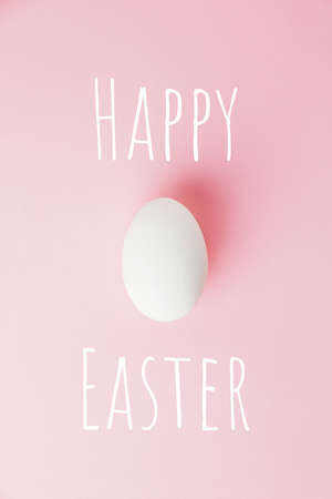 White Easter egg on pastel pink background. Happy Easter concept.