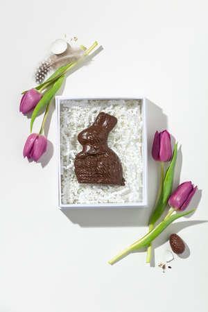 Easter composition with Pink tulips and chocolate bunny in gift box on white background Reklamní fotografie