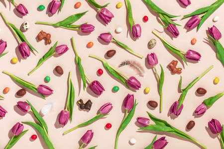 Easter composition with Pink tulips, chocolate eggs, bunnies and Jellybean pattern on pink background flat lay, top view.