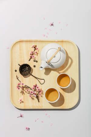 Tea concept, two white cups of tea and teapot on concrete background