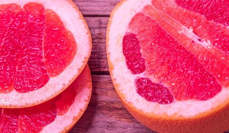A view from above of a fresh citrus fruit called grapefruit. Half fruit and two juicy slices side by side.