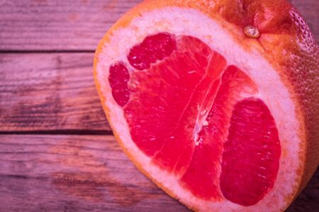 In the horizontal photo there is one fresh fruit. It's a grapefruit. It's juicy and ripe. A small part of the whole fruit is cut off, the flesh is visible