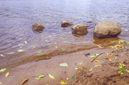 Four stones of different sizes lie on the water after each other
