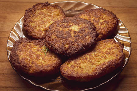 The photo shows fresh fried potato cutlets, with the addition of onion, one chicken egg, wheat flour. The cutlets were fried in a frying pan, greased with sunflower oil