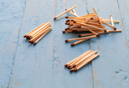 Matches, necessary in everyday life, lie small piles on a blue background