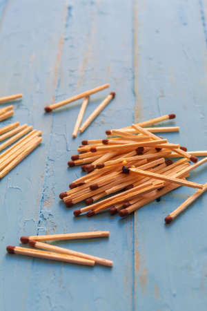 Wooden matches lying on a blue table, one match burns
