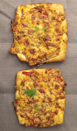 The vertical image shows two fresh mini pizzas. They lie on a light brown towel. Pizza has a square shape.