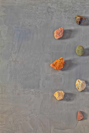 In the picture are stones, which were collected by a man near the river. There are a small number of stones. They are all of different colors, different shapes