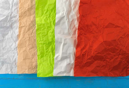 Five sheets of crumpled paper of different colours rest on a blue background