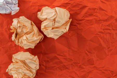 On a crumpled sheet of red paper lies heavily crumpled orange and white paper Foto de archivo