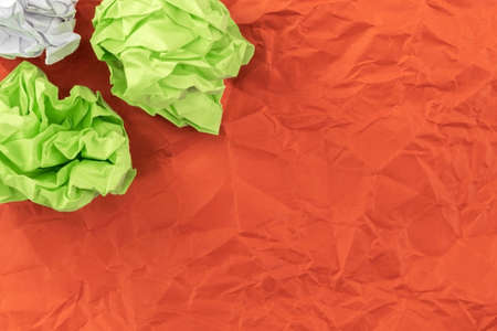 Two salad sheets of crumpled paper and one sheet of crumpled white paper lie on mint red paper
