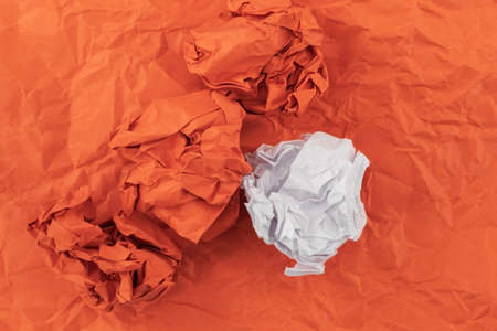 The colored paper is heavily crumpled on a crumpled paper background of red