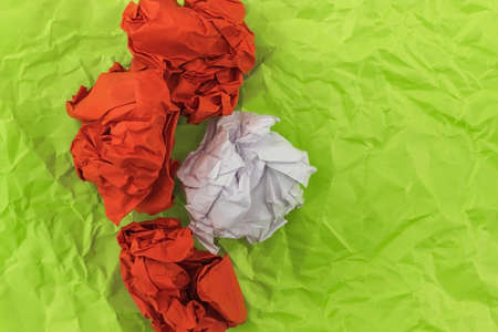 Three red heavily crumpled sheets of paper and one sheet of white lie on mint-colored paper Foto de archivo