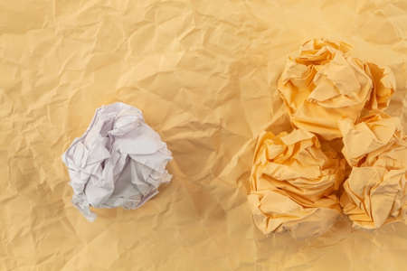 Three orange crumpled papers and one white paper lie on an orange paper background