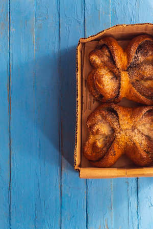 Two buns with sugar and poppy seeds are in a box on a wooden table
